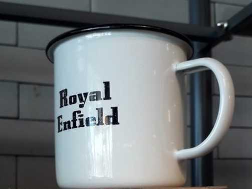 Taza blanca metálica vintage con logo de royal Enfield en color negro